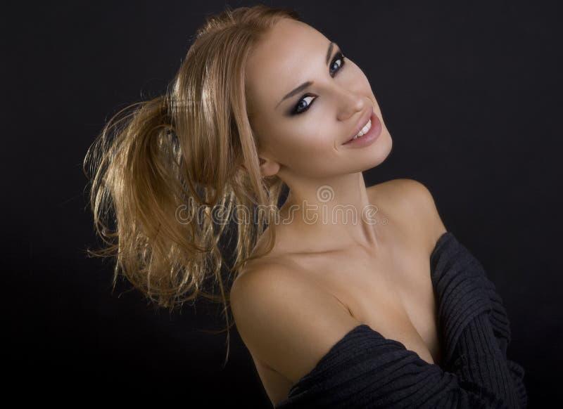 美丽的性感的白肤金发的微笑的妇女 可能 注视smokey 库存图片