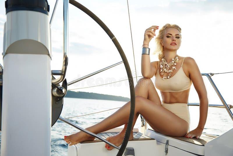 美丽的性感的年轻白肤金发的妇女,乘坐小船在水,日程,美好的构成,衣物,夏天,太阳,完善的身体fi 免版税库存图片