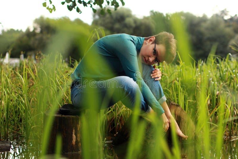 美丽的情感女孩坐在草和wate中的一个湖 图库摄影