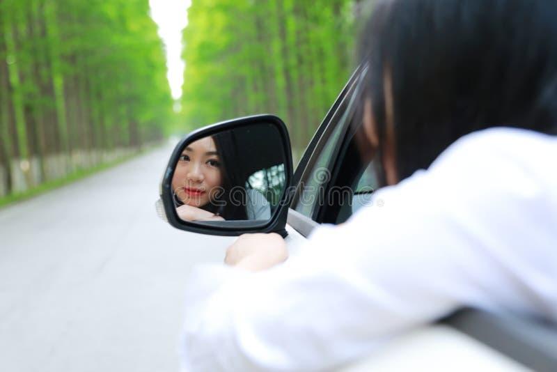 美丽的愉快的亚裔中国少妇坐白色汽车神色在她自己从汽车在夏天safty驱动的后视镜 免版税库存照片
