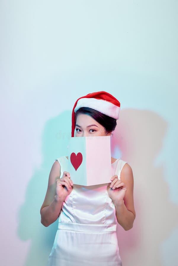 美丽的愉快的亚裔妇女在拿着爱lett的圣诞老人帽子 库存图片