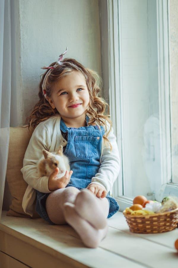 美丽的愉快的儿童女孩坐窗口基石并且拿着她的朋友小的五颜六色的兔子,复活节假日 图库摄影