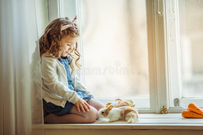 美丽的愉快的儿童女孩坐窗口基石并且拿着她的朋友小的五颜六色的兔子,复活节假日 免版税库存图片