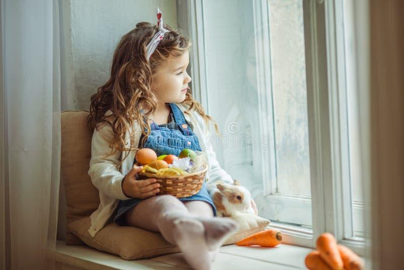美丽的愉快的儿童女孩坐窗口基石用她的朋友兔子并且拿着篮子用被绘的鸡蛋,复活节 库存图片