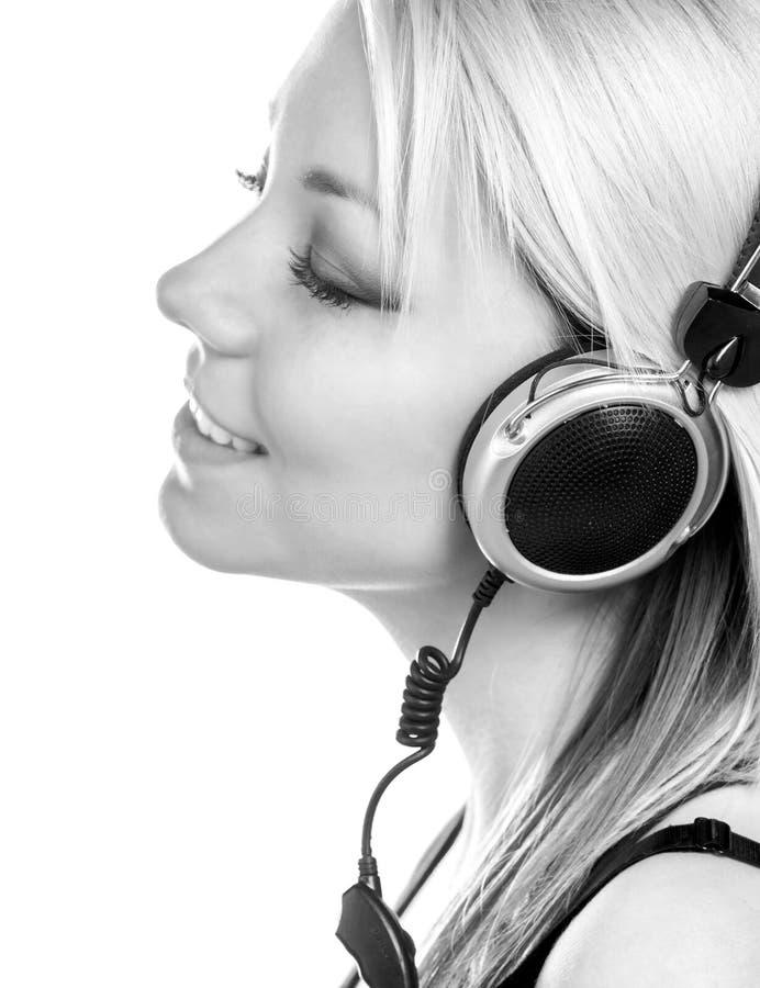 美丽的愉快的十几岁的女孩听到音乐通过耳机 免版税图库摄影