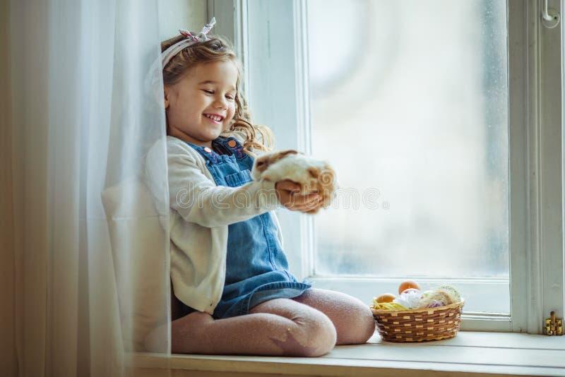 美丽的愉快的卷曲儿童女孩坐窗口基石用她的朋友小的五颜六色的兔子,复活节假日 免版税库存图片