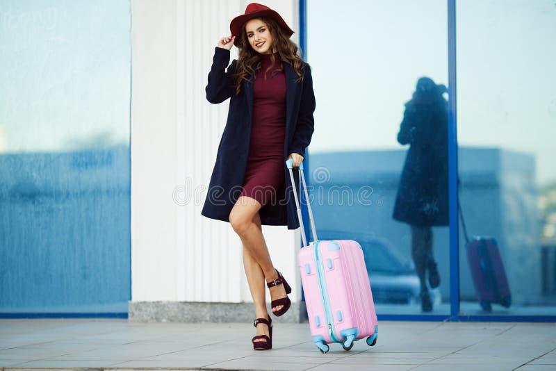 美丽的愉快的女孩在带着桃红色手提箱的机场大厦附近戴时尚衣裳和帽子 概念照片  图库摄影