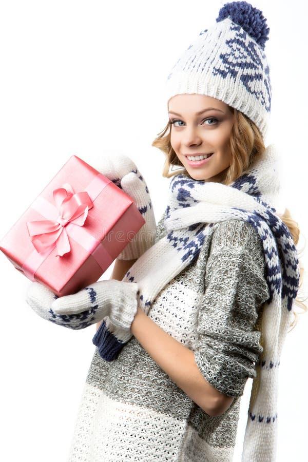 美丽的愉快的女孩画象毛线衣帽子和手套的有箱的圣诞节礼物 图库摄影