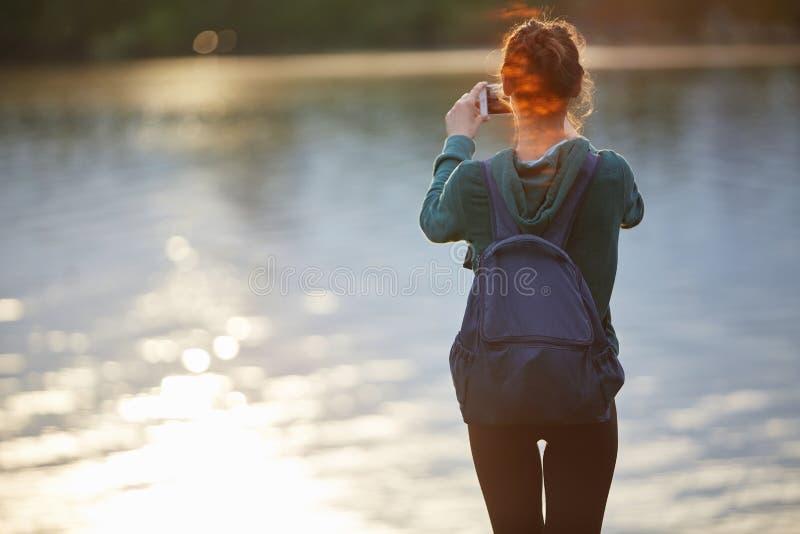 美丽的愉快的女孩画象运动服的在湖或海的岸 免版税库存照片