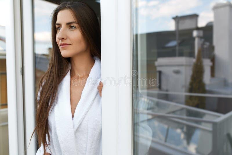 美丽的愉快的妇女在窗口的早晨在醒以后 库存图片