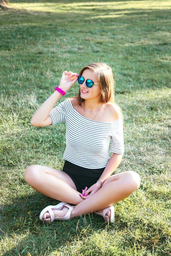 年轻美丽的愉快的妇女坐在太阳镜的草 免版税库存照片