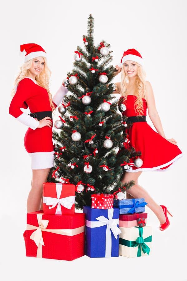 美丽的愉快的姐妹在圣诞树和礼物附近孪生 库存图片