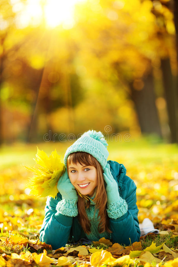 美丽的愉快的少妇在秋天公园 快乐的妇女wea 免版税库存图片