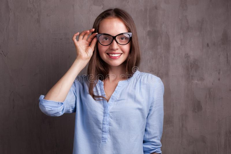 美丽的愉快的少妇画象戴眼镜的临近灰色背景墙壁 免版税库存图片