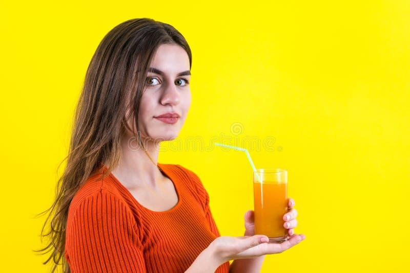 美丽的愉快的少年女孩用在黄色的橙黄汁液 库存图片