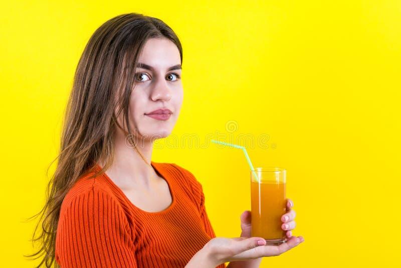 美丽的愉快的少年女孩用在黄色的橙黄汁液 免版税库存图片