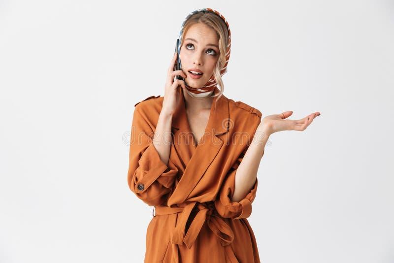 美丽的愉快的年轻女人佩带的丝绸围巾被隔绝在谈话白色的背景由手机 库存图片