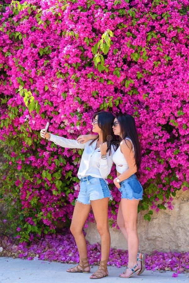 美丽的愉快的年轻女人在明亮的桃红色花五颜六色的自然本底做selfie  免版税库存图片