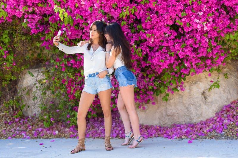 美丽的愉快的年轻女人在明亮的桃红色花五颜六色的自然本底做selfie  库存图片