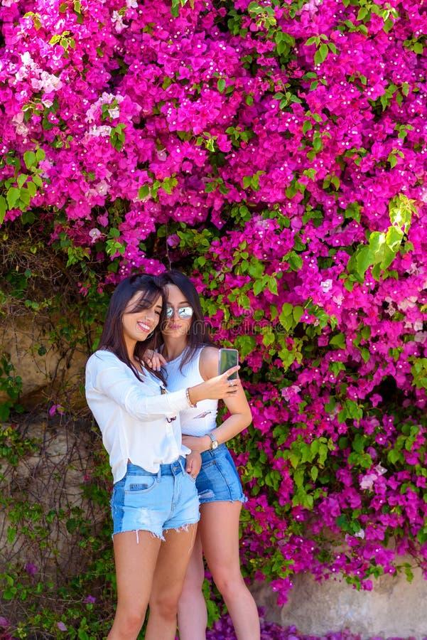 美丽的愉快的年轻女人在明亮的桃红色花五颜六色的自然本底做selfie  免版税库存照片