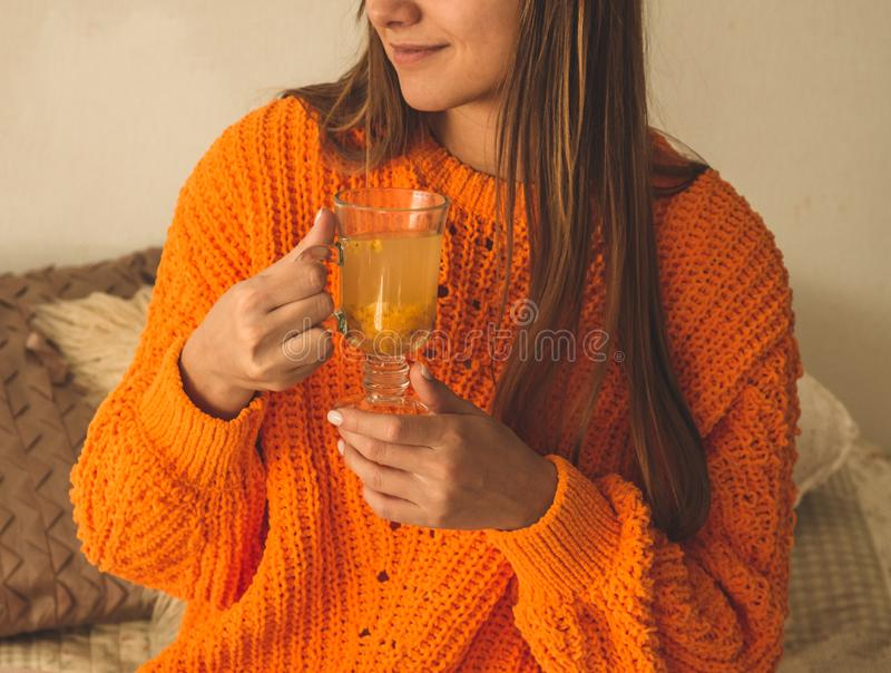 美丽的愉快的年轻女人饮用的咖啡或茶 在一件明亮的橙色毛线衣的床上 微笑的女孩特写镜头纵向 免版税库存图片