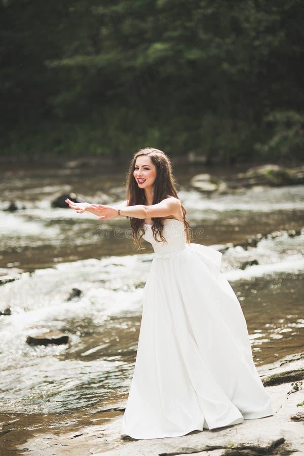 美丽的愉快的新娘户外在有岩石的一个森林里 婚姻的完美的日子 免版税图库摄影