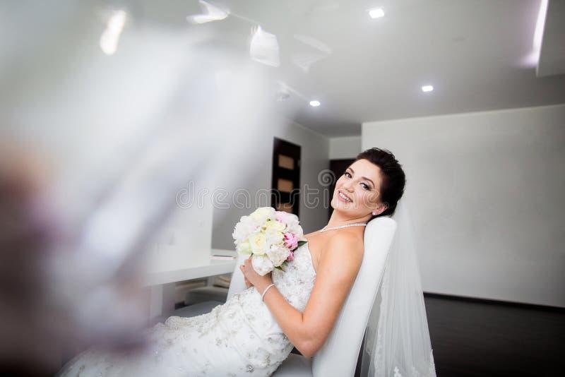 美丽的愉快的新娘画象坐沙发 库存图片