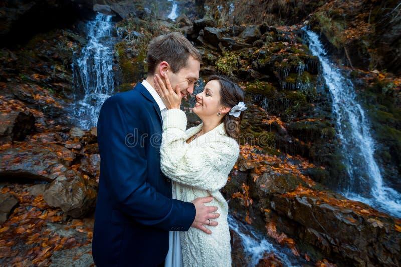 美丽的愉快的新娘软软接触她的新郎的面孔 在背景的瀑布 在山的秋天 免版税库存图片