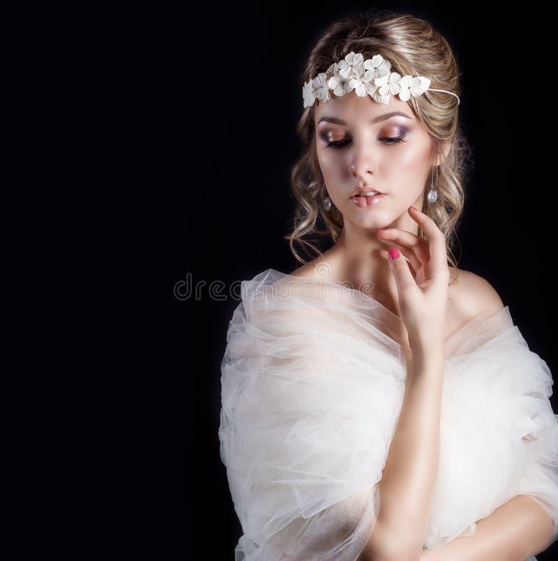 美丽的愉快的柔和的妇女新娘画象一根白色婚礼礼服c美丽的沙龙婚礼头发的有在她的白花的 库存图片