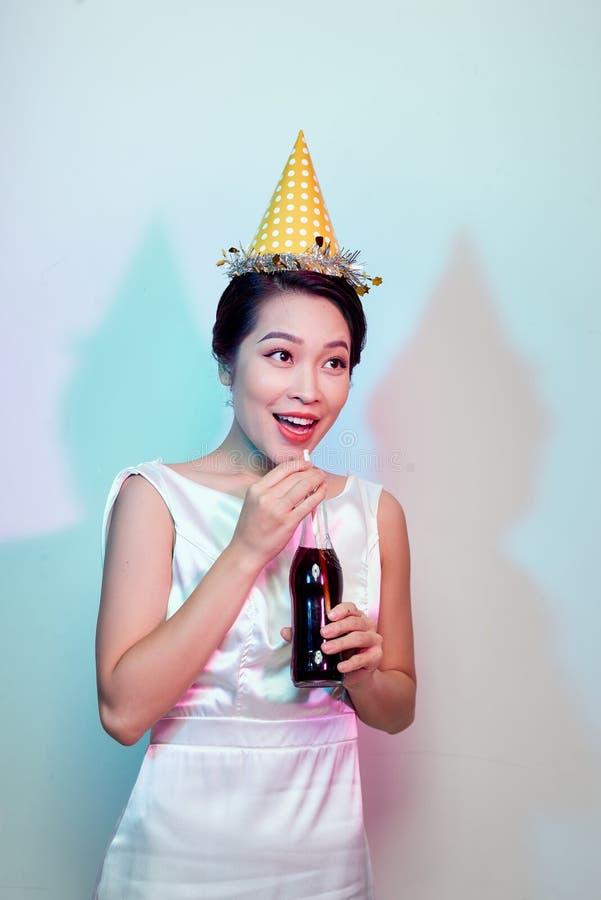 美丽的愉快的逗人喜爱的亚裔妇女画象在从瓶的白色,饮用的可乐隔绝的便服的有秸杆的 免版税库存照片