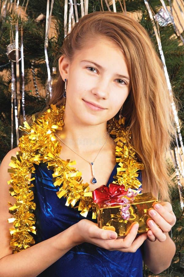 美丽的愉快的青少年的女孩在本身前拿着圣诞节礼物 库存图片