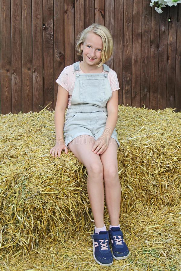 美丽的愉快的青春期前的女孩在短的围嘴总体穿戴了坐一把干草在村庄 乡村模式 免版税库存图片