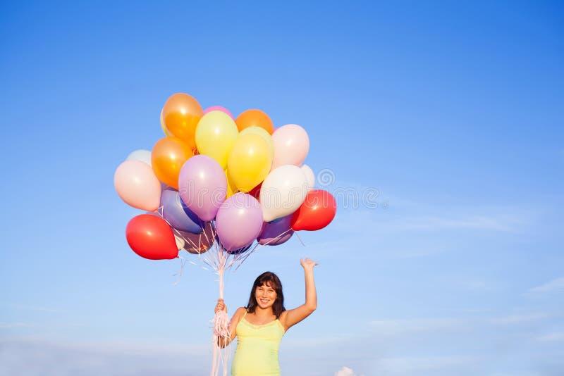 美丽的愉快的年轻孕妇女孩户外与气球 免版税库存图片