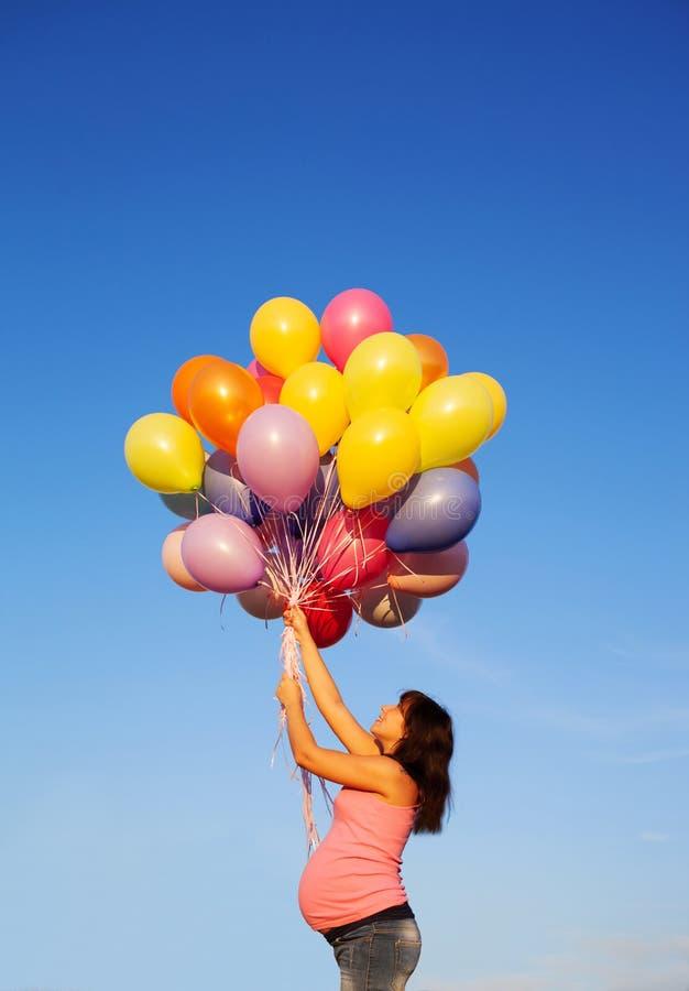 美丽的愉快的年轻孕妇女孩户外与气球 免版税库存照片