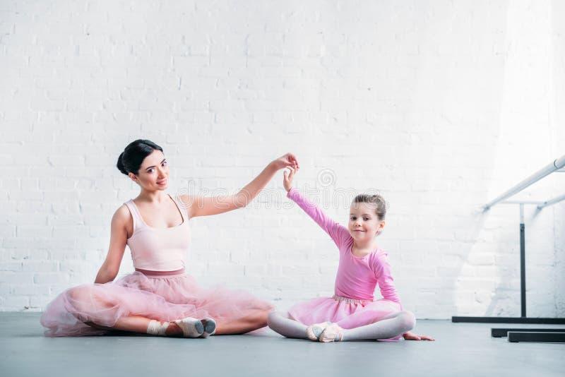 美丽的成人和小芭蕾舞女演员坐和微笑对照相机的桃红色芭蕾舞短裙裙子的 库存图片