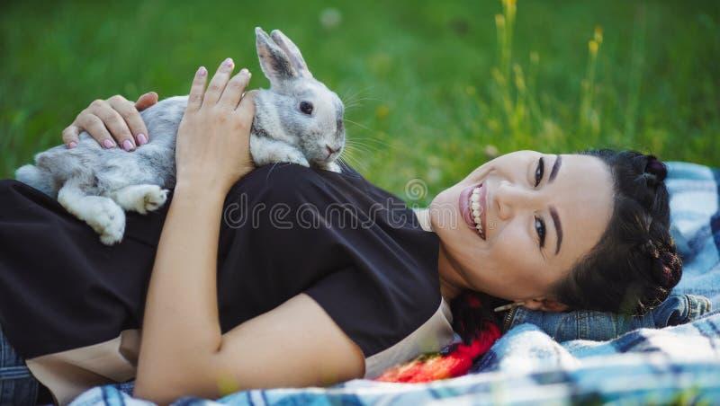 美丽的成熟亚裔妇女在地面放置并且拥抱兔子 免版税库存图片