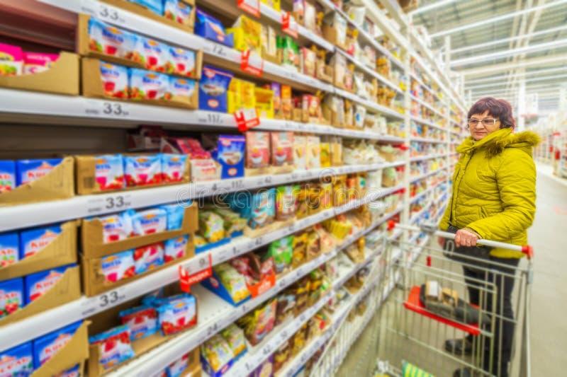 美丽的成熟妇女在一个购物中心选择不同的好吃的东西 免版税库存照片