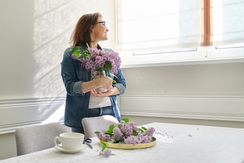 美丽的成熟妇女在家有淡紫色花花束的在花瓶饮用的咖啡的 免版税库存图片