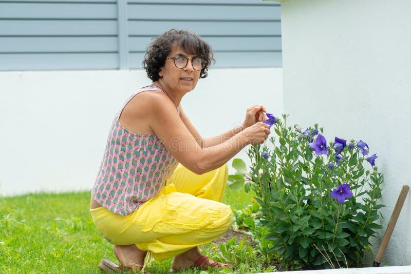 美丽的成熟妇女在有花的一个庭院里 免版税库存照片