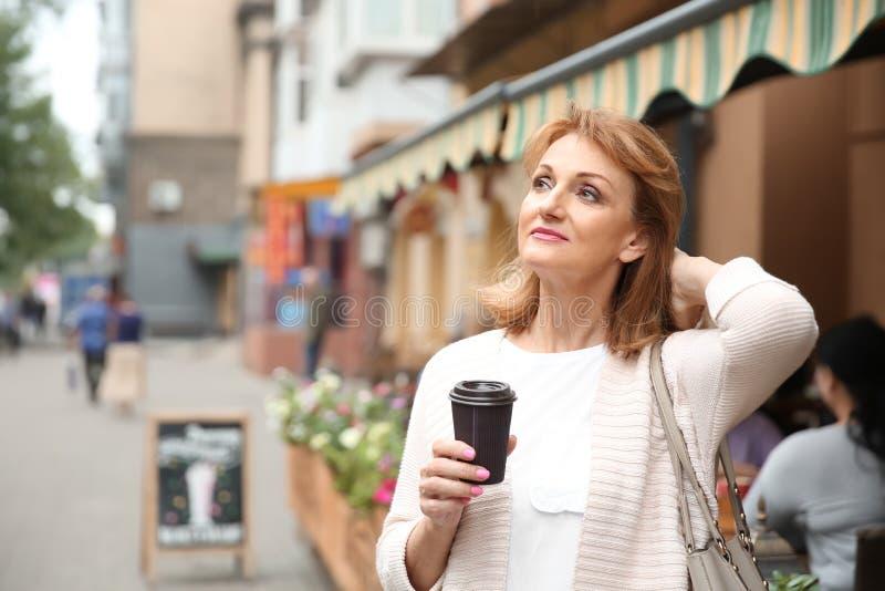 美丽的成熟妇女饮用的咖啡户外 库存图片