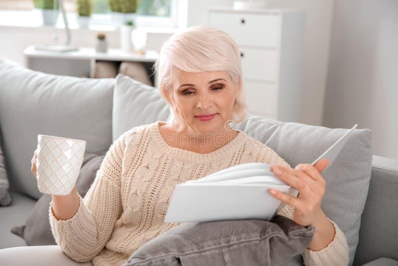 美丽的成熟妇女饮用的咖啡,当看书在家时 免版税库存图片