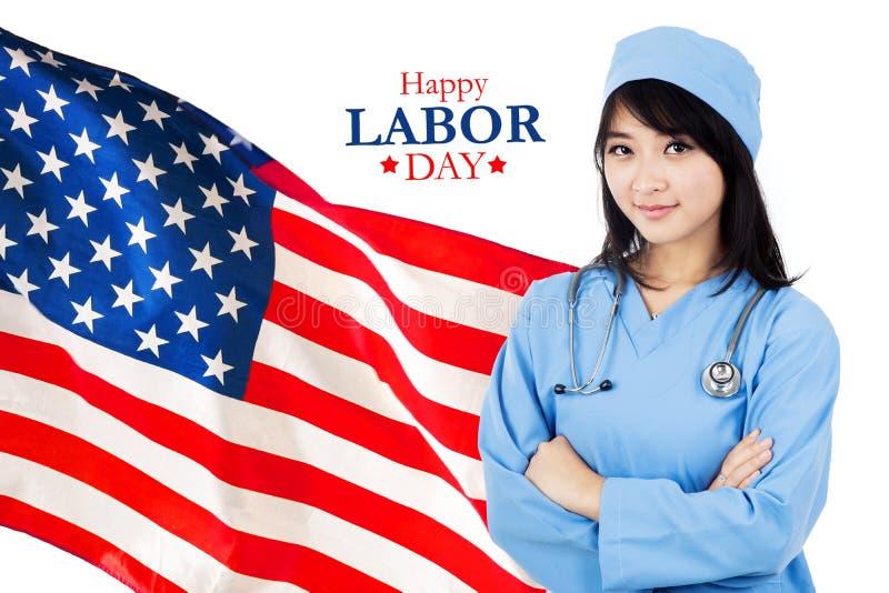 美丽的护士站立与愉快的劳动节文本 免版税库存照片