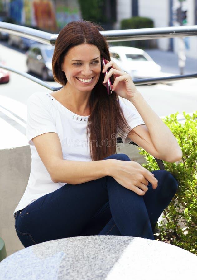 美丽的拉提纳妇女谈话在手机 免版税图库摄影