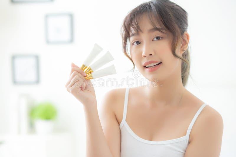 美丽的拿着和当前奶油或化妆水产品,秀丽亚洲女孩展示化妆构成的画象年轻亚裔妇女 免版税库存图片
