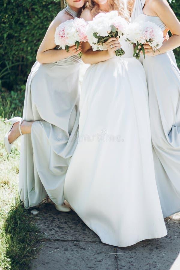美丽的拿着时髦的牡丹花束的女傧相和新娘 免版税库存图片