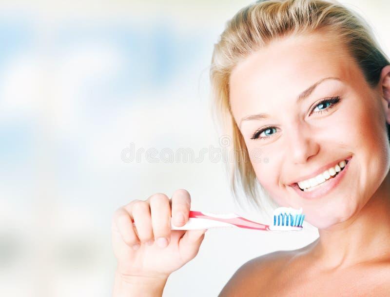 美丽的掠过的女孩她的牙 免版税库存照片