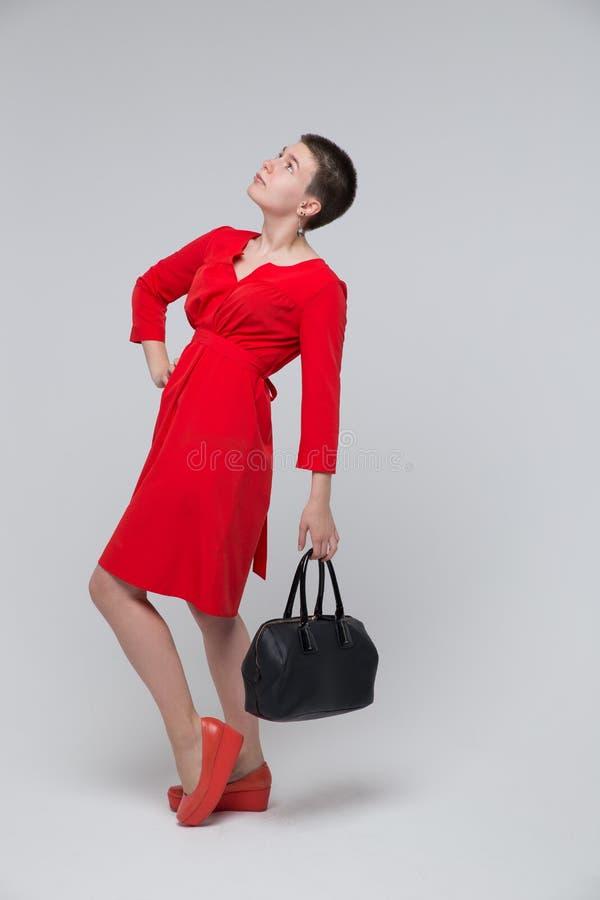 美丽的摆在有袋子的演播室的女孩红色礼服 免版税库存照片