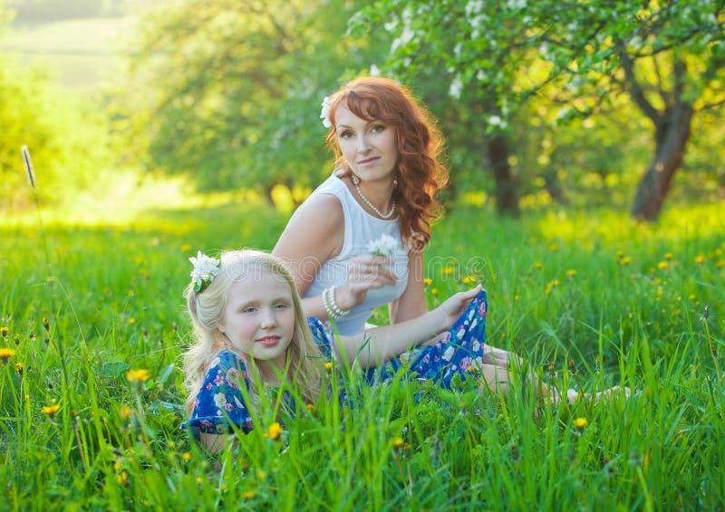 美丽的摆在母亲和她逗人喜爱的女儿微笑和 免版税图库摄影