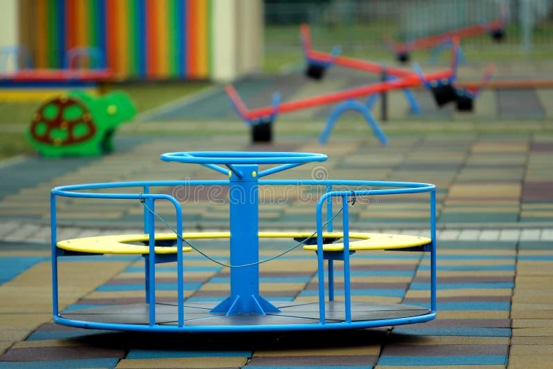 美丽的操场在有软的路面、明亮的摇摆、环形交通枢纽和长凳的幼儿园在好日子 完善的地方为 免版税库存图片
