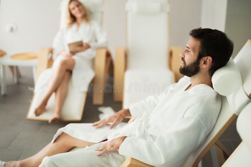 美丽的放松在温泉的妇女和英俊的人集中 免版税库存图片